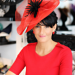celebrity milliner in a tight red top wearing a red hat of her own creation